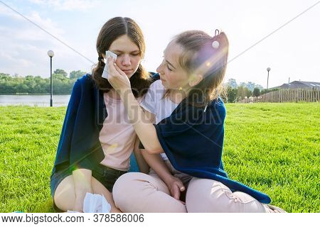 Crying Teenager Girl And Comforting Girlfriend, Teenagers Sitting On The Grass In The Park. Friendsh