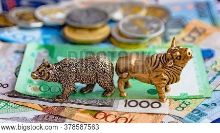 Bull And Bear As Symbols Of Stock Trading On A Blurred Background Of Price Graphics. The Concept Of