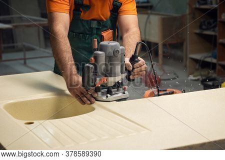 Stone sink furniture production. Carpenter polishes the surface of the sink with a grinder