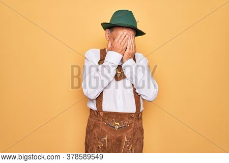 Senior grey-haired man wearing german traditional octoberfest suit over yellow background rubbing eyes for fatigue and headache, sleepy and tired expression. Vision problem