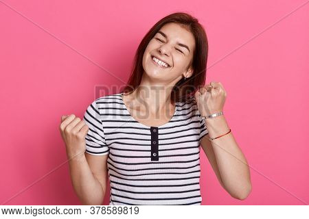 Excited Cheerful Female With Joyful Expression, Cheers And Clenches Fists, Celebrating Her Success,