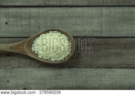 Uncooked Dry Thai Jasmine Rice In Wooden Ladle Isolated On Wood Floor Background, Flat Lay And Top D