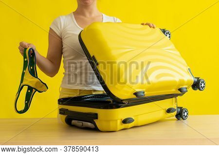 Faceless Woman Folds Bikini In A Suitcase On A Yellow Background. The Girl Is Packing Luggage For A