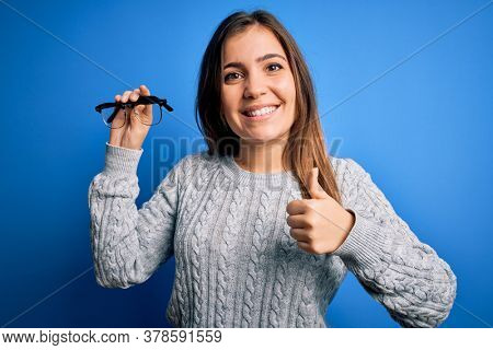 Young blonde woman holding eyewear optical glasses over blue isolated background happy with big smile doing ok sign, thumb up with fingers, excellent sign