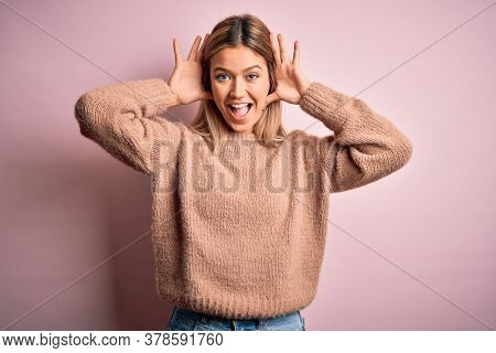 Young beautiful blonde woman wearing winter wool sweater over pink isolated background Smiling cheerful playing peek a boo with hands showing face. Surprised and exited
