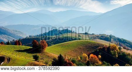 Mountainous Rural Landscape In Autumn. Fields On Rolling Hills. Fence Along The Path. Trees In Color