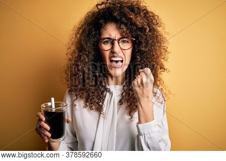 Young beautiful woman with curly hair and piercing wearing glasses drinking glass of coffee annoyed and frustrated shouting with anger, crazy and yelling with raised hand, anger concept