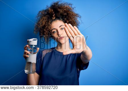 Young beautiful sporty woman with curly hair and piercing doing sport holding bottle of water with open hand doing stop sign with serious and confident expression, defense gesture