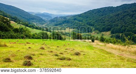 Country Road Through Rural Field. Suburban Summer Landscape In Mountains. Village In The Distant Val