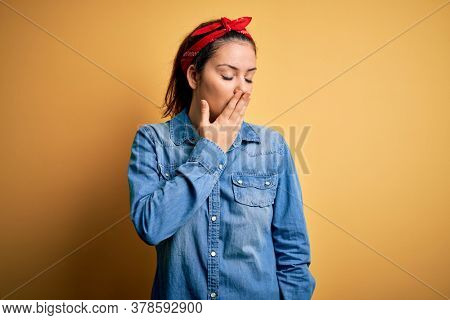 Young beautiful brunette woman wearing casual denim shirt and hair handkerchief bored yawning tired covering mouth with hand. Restless and sleepiness.