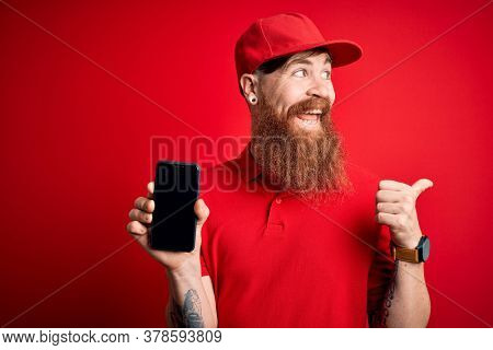 Redhead Irish delivery man with beard holding smartphone showing app on screen pointing and showing with thumb up to the side with happy face smiling