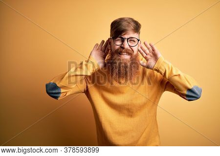 Handsome Irish redhead man with beard wearing glasses over yellow isolated background Trying to hear both hands on ear gesture, curious for gossip. Hearing problem, deaf