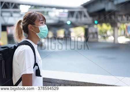 Asian Woman With Surgical Face Mask, Carrying Backpack,  Traveling To The City Standing Nearby Inter
