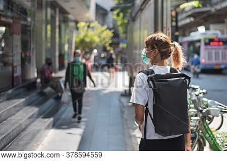 Asian Woman With Surgical Face Mask Feel Tired Walking At Street, Carrying Backpack, Traveling To Th