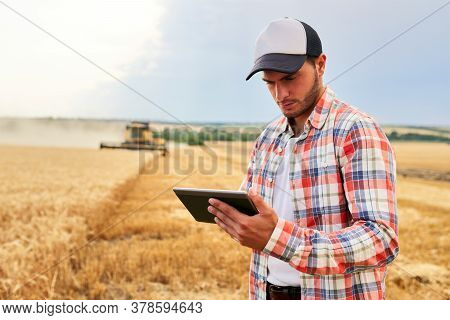 Precision Farming. Farmer Holding Tablet For Combine Harvester Guidance And Control With Modern Auto