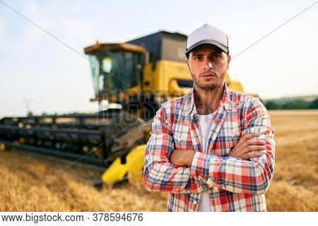 Portrait Of Proud Harvester Machine Driver With Hands Crossed On Chest. Farmer Standing At His Combi