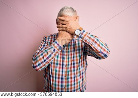 Senior handsome hoary man wearing casual colorful shirt over isolated pink background Covering eyes and mouth with hands, surprised and shocked. Hiding emotion