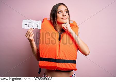 Young beautiful brunette woman wearing lifejacket holding paper with help word message serious face thinking about question, very confused idea