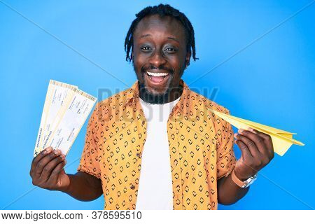 Young african american man with braids holding paper airplane and boarding pass smiling and laughing hard out loud because funny crazy joke.