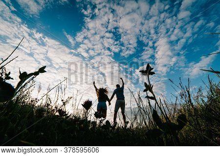 Rear View Of A Romantic Man And Woman Walking Away On Field Grass, Nature Enjoying Stunning Sunset.
