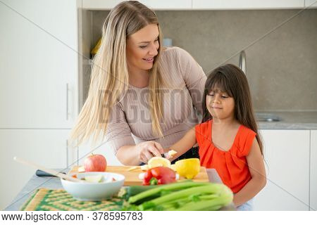 Cheerful Mom Teaching Daughter To Cook Salad. Girl And Her Mother Cutting Fresh Vegs At Kitchen Tabl