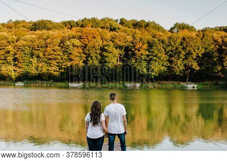 Couple Holding Hands Standing Back And Looking Away On Lake. Portrait Of A Romantic Young Man And Wo