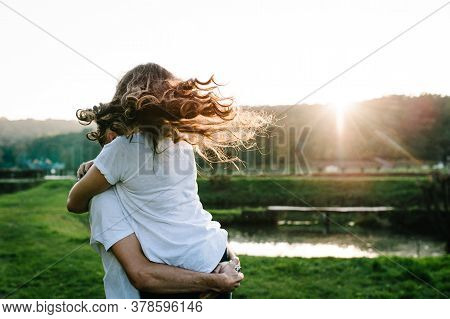 Photo Young Married Couple Hugging, Husband And Wife Holding Hands On A Near Lake. Close Up. Summer