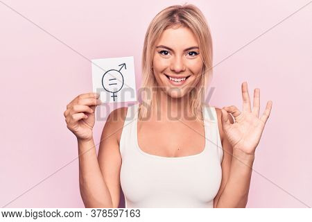 Young blonde woman asking for sex discrimination holding paper with gender equality message doing ok sign with fingers, smiling friendly gesturing excellent symbol