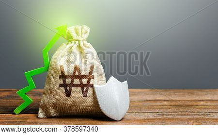 South Korean Won Money Bag With A Shield And A Green Arrow Up. Safety Security Of Investments, Finan