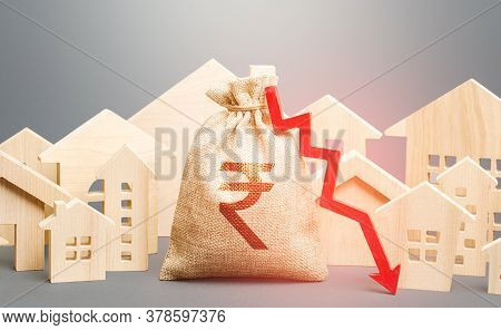 City Residential Buildings And Indian Rupee Money Bag With A Red Down Arrow. Low Cost Of Real Estate