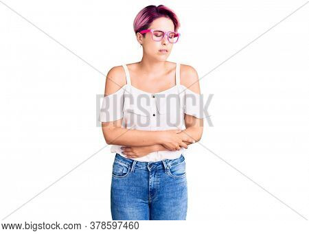 Young beautiful woman with pink hair wearing casual clothes and glasses with hand on stomach because indigestion, painful illness feeling unwell. ache concept.