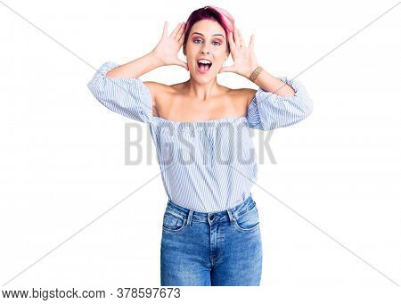 Young beautiful woman with pink hair wearing casual clothes smiling cheerful playing peek a boo with hands showing face. surprised and exited