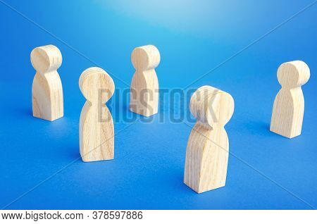 Wooden Figurines Of People Stand On A Blue Background. Loneliness And Disconnection. Safe Spacing Be