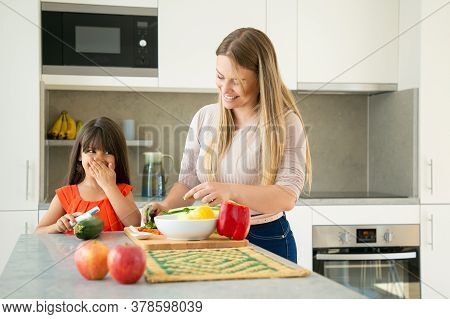 Cheerful Mom And Daughter Chatting And Laughing While Cooking Vegetables For Dinner. Girl And Her Mo