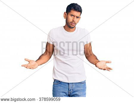 Young latin man wearing casual clothes clueless and confused with open arms, no idea concept.