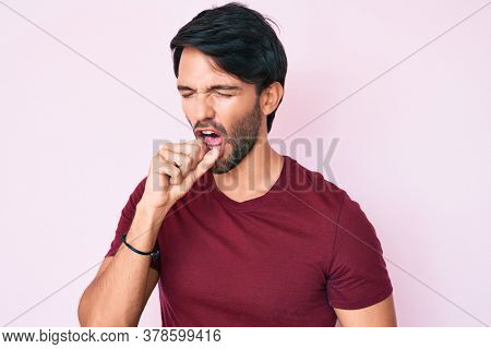Handsome hispanic man wearing casual clothes feeling unwell and coughing as symptom for cold or bronchitis. health care concept.