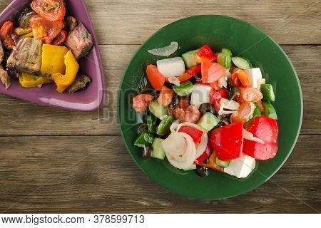 Greek Salad On Brown Wooden Background . Greek Salad On Green Plate With Vegetarian Salad Top View .