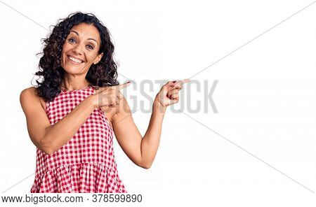 Middle age beautiful woman wearing casual sleeveless t shirt smiling and looking at the camera pointing with two hands and fingers to the side.