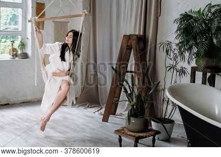 Tender And Calm Young Adult Female In White Bathrobe Sitting On A Hanging Swing At Home, Resting On