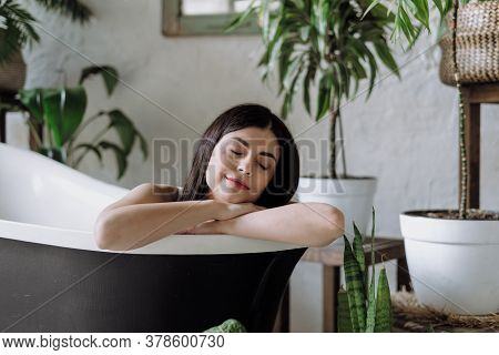 Portrait View Of Calm Young Adult Woman Lying In Bath, Making Closed Eyes Enjoying Morning Skin And
