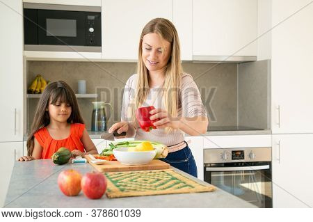 Mom Showing Daughter How To Cook Salad For Dinner. Girl And Her Mother Cutting Vegs On Kitchen Count