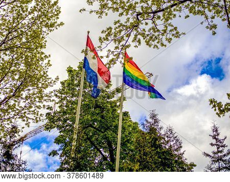 Lgbt And Holland Flags On Poles Blow In The Wind. Symbol Of Tolerant. Gay Sign Rainbow. The Rainbow