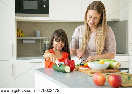 Positive Mom And Daughter Cooking Vegetables For Dinner, Smiling And Talking. Girl And Her Mother Pe