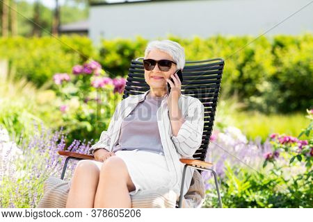 technology, old age and people concept - happy smiling senior woman in sunglasses calling on smartphone resting at summer garden