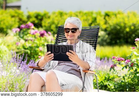 technology, old age and people concept - happy smiling senior woman with tablet pc computer resting at summer garden