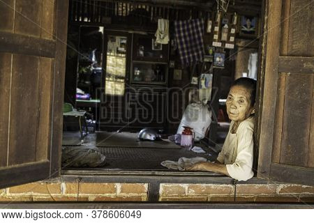 Bagan/myanmar-october 5th 2019: An Elderly Burmese Woman Is Sitting By The Window Of The House.