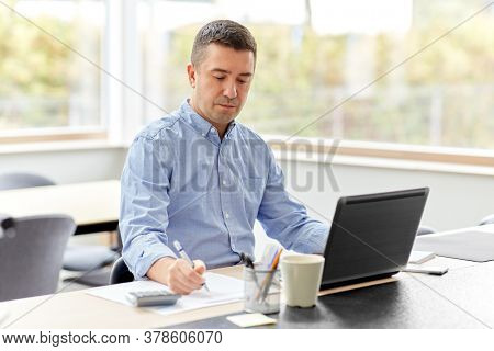 remote job, business and people concept - middle-aged man with calculator, papers and laptop computer working at home office