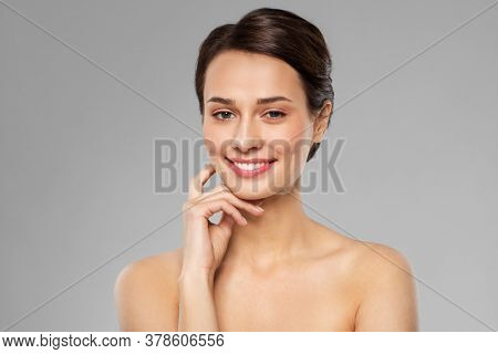 beauty, bodycare and people concept - beautiful young woman touching her face over grey background