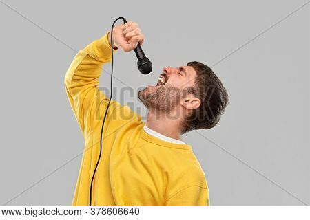 music and people concept - young man in yellow sweatshirt with microphone singing over grey background