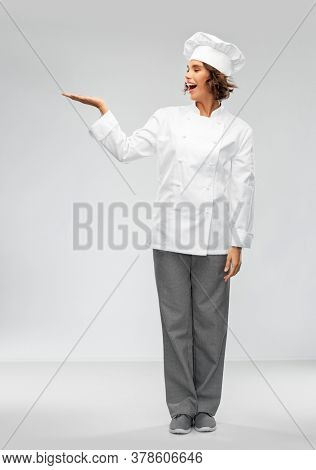 cooking, advertisement and people concept - happy smiling female chef holding something on palm of hand over grey background